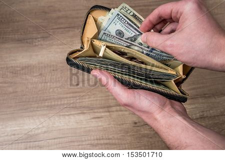 man hold full wallet with us dollar