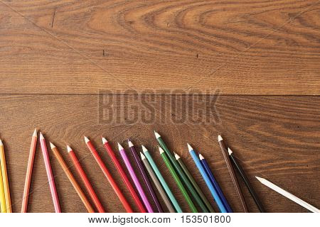 Colorful Pencils On The Brown Wooden Table Background. Frame Of Colored Pencils Over Wood With Free