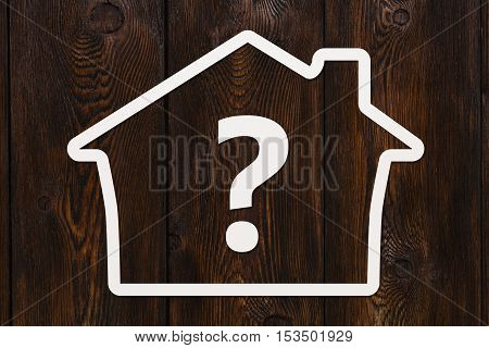 Paper house with question sign inside. Dark wooden background. Abstract housing conceptual image