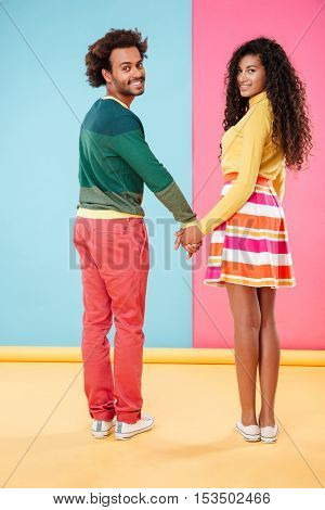 Smiling african young couple holding hands and looking back over colorful background