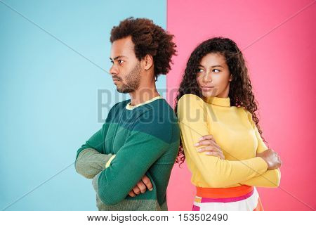 Sad unhappy african young couple standing with arms crossed