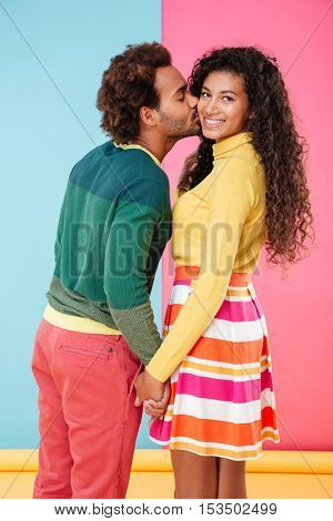 Happy african young couple kissing and holding hands over colorful background