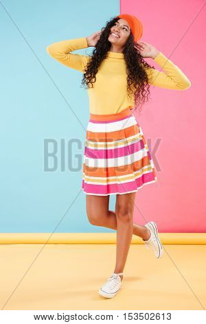 Full length of smiling pretty girl in hat with long curly hair standing over colorful background