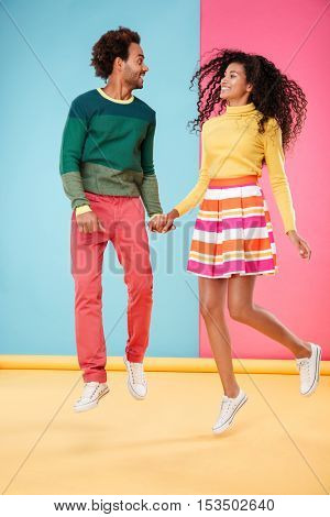 Cheerful curly african young couple in bright clothes jumping together