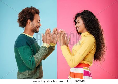 Smiling african american young couple playing patty cake