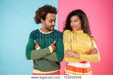 Happy young couple standing with arms crossed and looking at each other