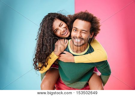 Portrait of happy african american young couple having fun and winking