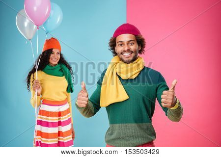 Happy african young man showing thumbs up while smiling girl with balloons standing on background