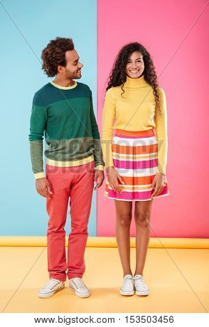 Full length of happy cute african young couple standing and smiling over bright colorful background