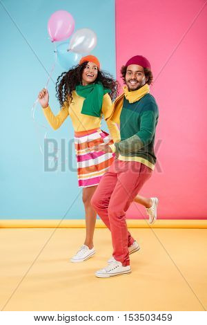 Happy african american young couple in hats and scarves holding balloons and running