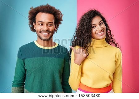 Cheerful curly young womna standing and pointing on her boyfriend over colorful background