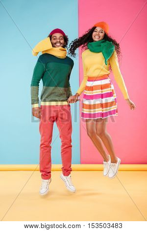 Cheerful african american young couple in hats and scarves jumping together