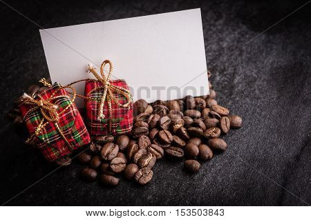 Red gift box and blank paper with roasted coffee beans on dark background can be used as a background