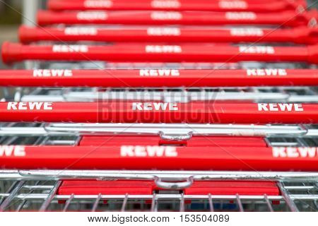HANNOVER / GERMANY - OCTOBER 18 2016: Shopping carts of the german supermarket chain Rewe stands together in a row on parking area.
