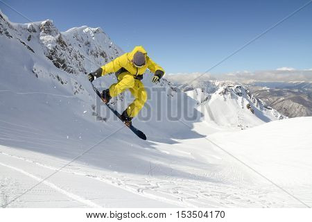 Snowboarder jumping on mountains. Extreme snowboard freeride sport.