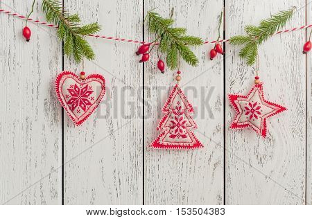 Christmas toys (christmas tree, heart, star) hanging over wooden background.
