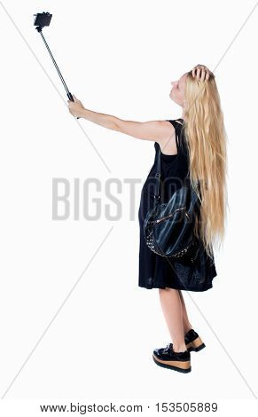 back view of standing young beautiful girl with tablet computer in the hands of. girl  watching. Rear view people collection. Isolated over white background. girl with a leather backpack makes selfie