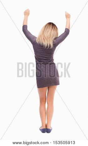 Back view of  business woman.  Raised his fist up in victory sign.    Raised his fist up in victory sign.   Isolated over white background. The girl in a dress held up his hands.