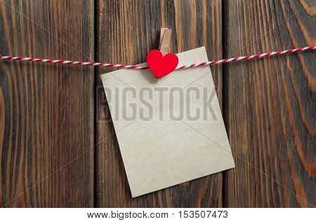 Paper sheet with heart hanging on rope on wooden background. Valentines day card.