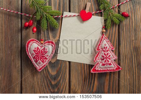 Christmas decorations hanging with blank sheet of paper on rope on wooden background.