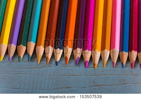 Wooden colorful pencils, on a blue old table