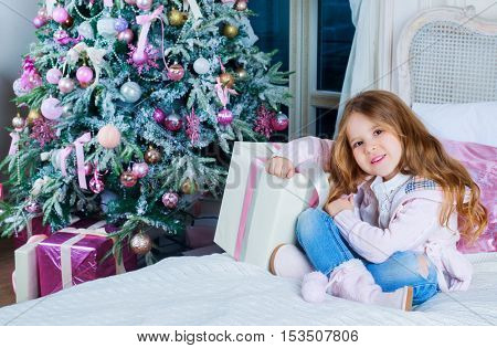 happy girl at home with Christmas tree and presents