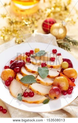 Border of baked chicken breast with baked fruits sage and spices on plate.