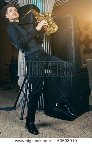 Young man plays a musical instrument saxophone. Saxophone instrument for jazz.