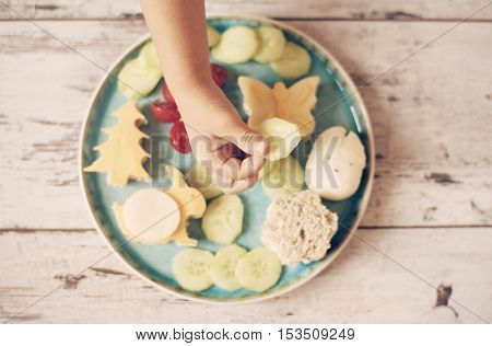 Creative Idea For Child Food. Funny Breakfast. Children's Hand Holds Cucumber. Sandwiches In The Sha