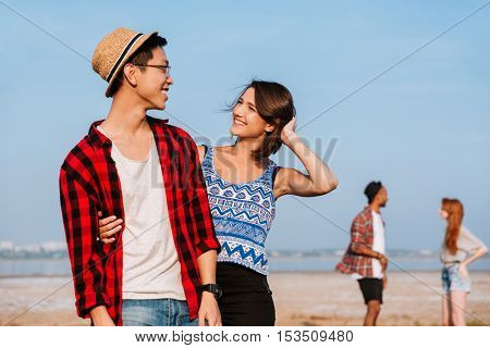 Two happy young couples standing and smiling outdoors