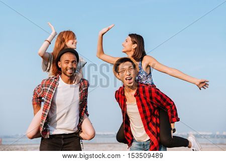 Two happy young couples giving high five and having fun outdoors
