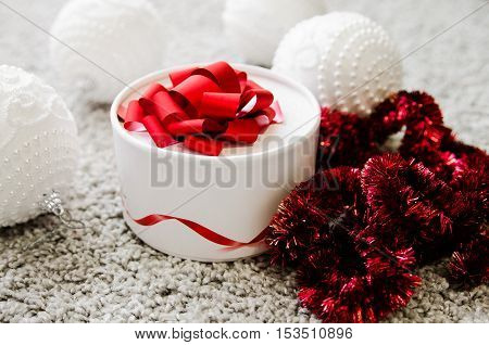 White box with a red ribbon for gift. Christmas decorations