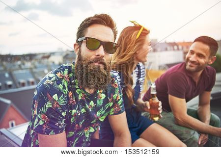 Handsome bearded man in colorful shirt and sunglasses sitting with friends on roof