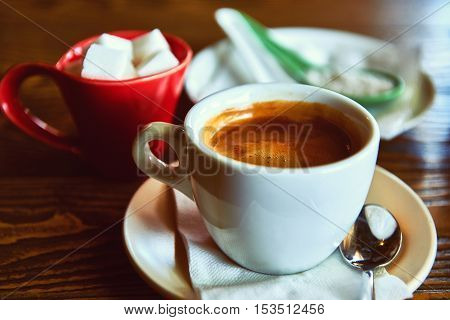 Cup of coffee and sugar on a wooden table