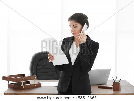 Successful mature businesswoman with mobile phone and documents in her office