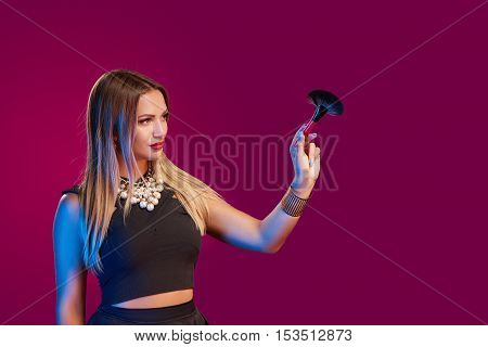 Portrait of glamourous female makeup artist painting with a brush on blank copy space
