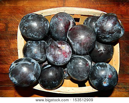 Big blue plums packed in a wooden basket. Fresh fruits and juicy