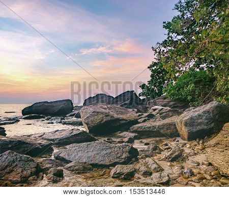 Tropical colourful sunset on the White Sand Beach Koh Chang islandThailand. View of dark night sea with protruding stones