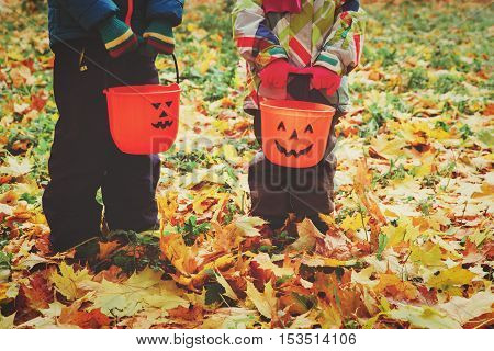 little boy and girl trick or treating in fall nature, halloween concept