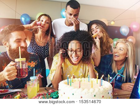 Excited young adult woman blowing on candles in cake with white frosting after making a wish while surrounded by friends