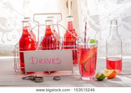 Tasty red orangeade in bottle with citrus fruit on wooden table