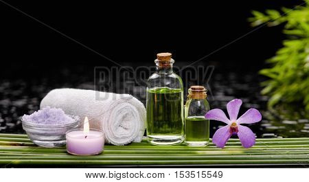bamboo grove with orchid ,candle ,massage oil ,bamboo leaf on wet background