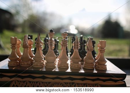 sun glare on the figures in the figures chess board in the park spring evening