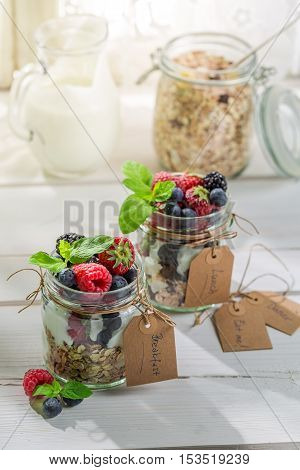 Tasty granola with fruits and yogurt on wooden table