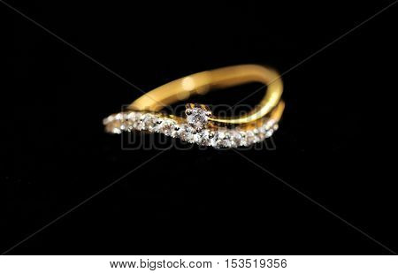 Gold engagement ring with diamond on an isolated black background