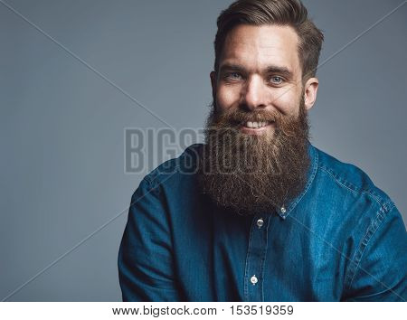 Single sitting young handsome serious man in blue denim shirt and beard over gray background with copy space