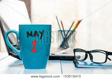 May 1st. Day 1 of month, calendar on morning coffee cup, business office background, workplace with laptop and glasses. Spring time, empty space for text.