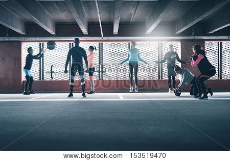 Group of diverse friends working out in town in a commercial building doing a variety of different exercises weightlifting skipping and throwing ball