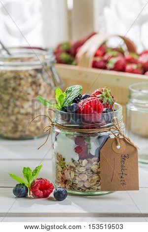 Fresh muesli with fruits and yogurt on wooden table