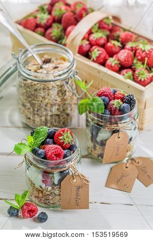 Fresh granola with yogurt and fruits on wooden table